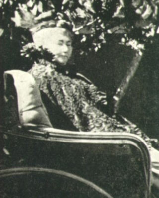 Sarah Winchester sits in a chair in a black and white  photo